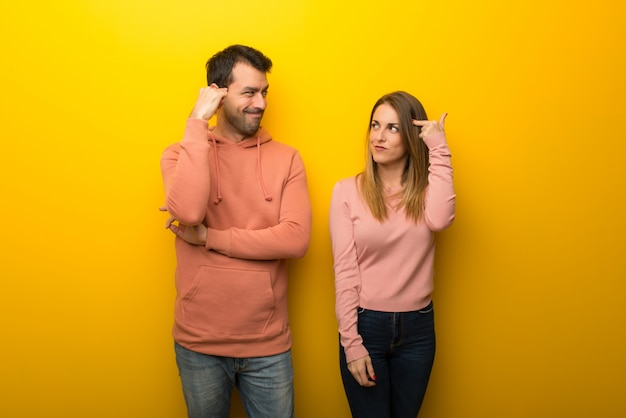 Group of two people on yellow background making the gesture of madness