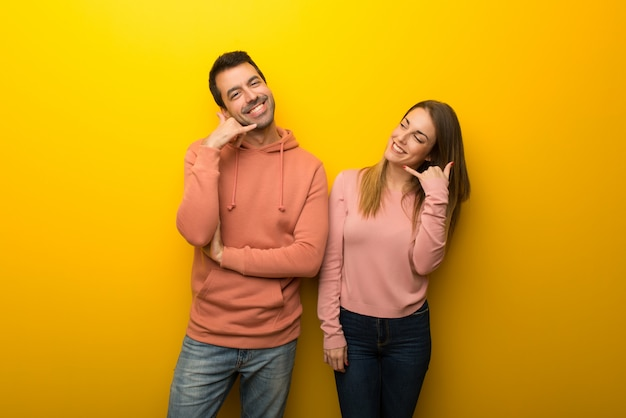 Group of two people on yellow background making phone gesture. call me back sign