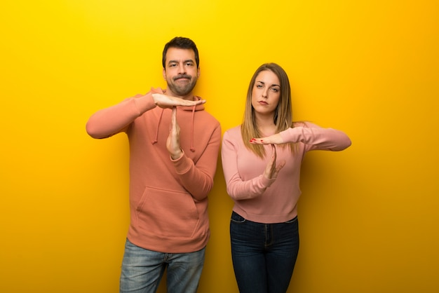 Group of two people on yellow background making stop gesture