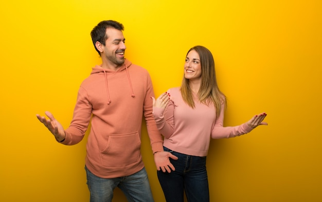 Group of two people on yellow background proud and self-satisfied