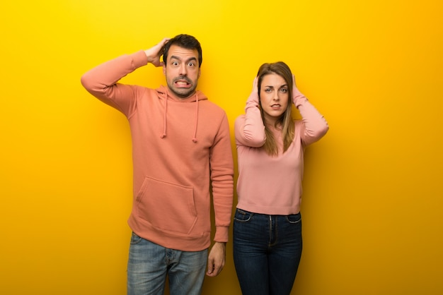 Group of two people on yellow background takes hands on head because has migraine