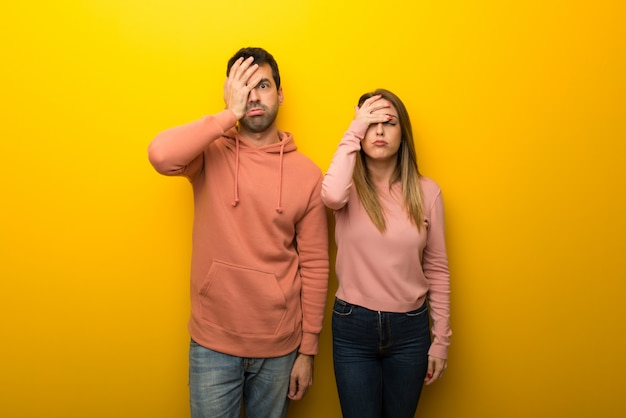 Group of two people on yellow background with surprise