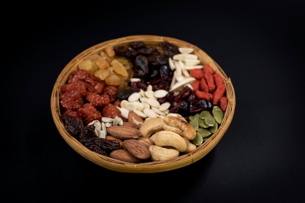 Group of various types of whole grains and dried fruits on a bamboo tray on black background.