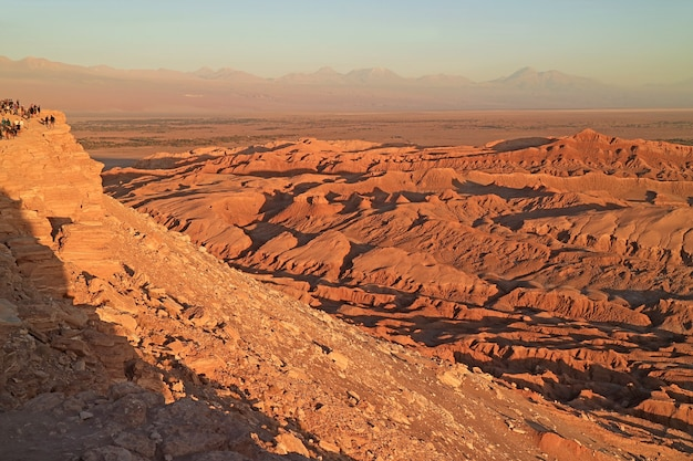 Group of visitors on the cliff waiting for the amazing sunset at the moon valley or valle de la luna in atacama desert, northern chile