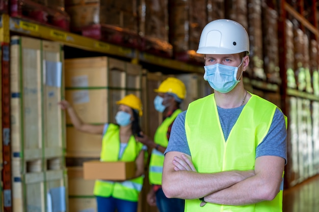 Group warehouse workers wearing protective mask working in industrial factory or warehouse.