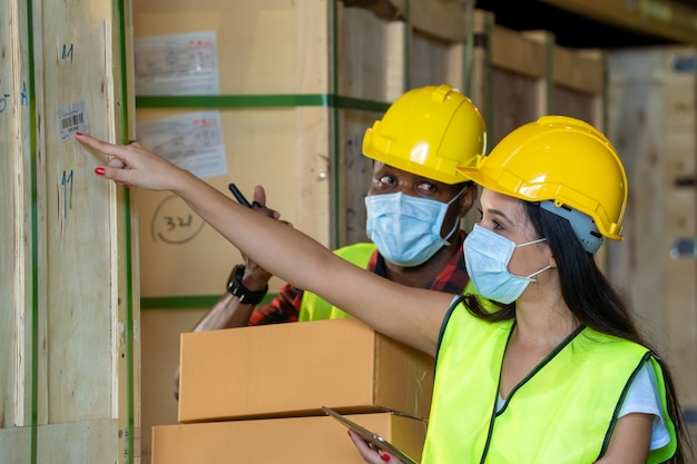 Group warehouse workers wearing protective mask  working together at warehouse,coronavirus has turned into a global emergency.
