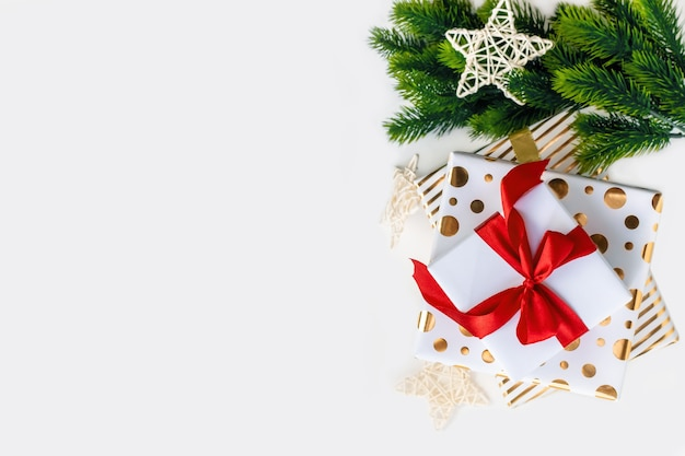 A group of white and gold gift boxes tied with a red ribbon bow and christmas tree branches on a light background with copy space. top view, flat lay. xmas decoration, festive backdrop.