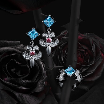 Group of white gold rings and earrings with topaz, garnets and diamonds on natural roses black background, included clipping path.