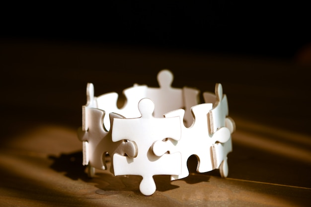 Group of white jigsaw puzzle on wooden table. business teamwork and collaborate  concept.