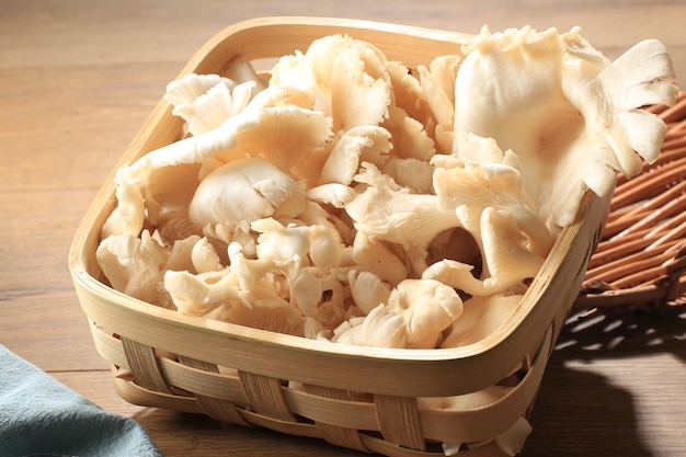 A group of white oyster mushroom on wicker basket on brown wooden table ready to cook in the kitchen