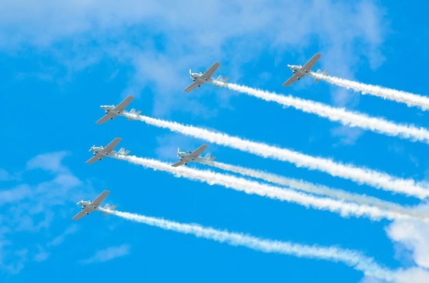 Group of white turboprop aircraft with a trace of white smoke against a blue sky.