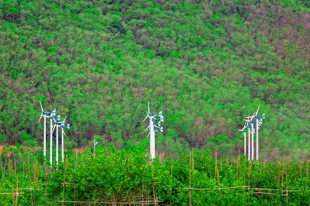Group of white wind turbines with fruit garden in foreground