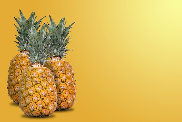 Group of whole and fresh pineapples with orange background and lateral space for text