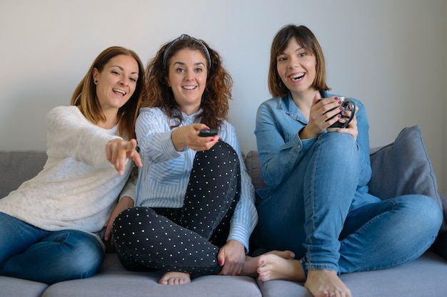 Group of women choosing a film and talking about cinema at home.