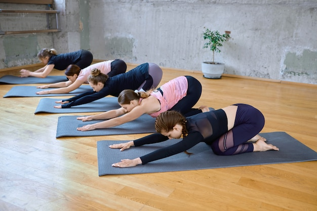 Group of women doing child pose in hall.