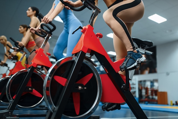 Group of women doing exercise on a stationary bikes in gym,