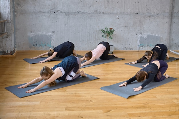 Group of women doing stretching exercise in hall.