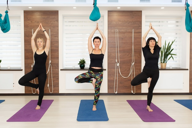 Group of women doing yoga exercises in gym