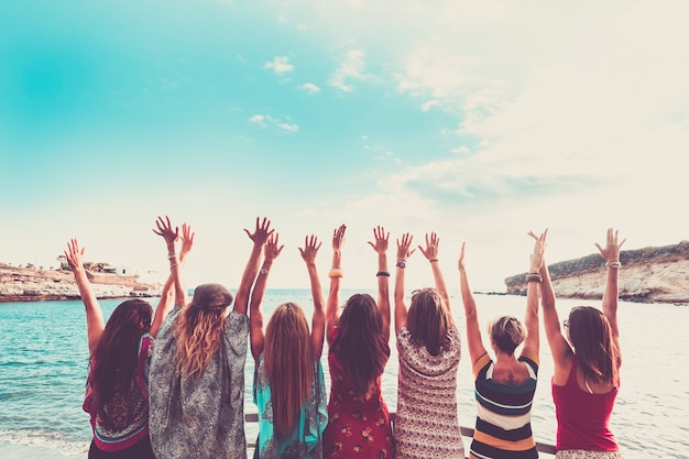 Group of women enjoying and celebrate summer vacation all together saying hallo to the ocean and the nature young people leisure activity all hands up and vintage colors style fashion dresses