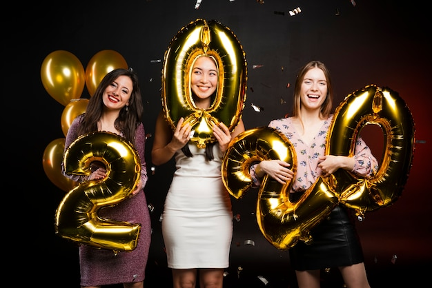 Group of women at new years party holding balloons