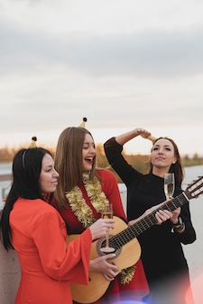Group of women playing the guitar on the rooftop party