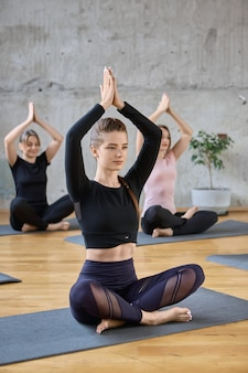 Group of women practicing yoga in hall.