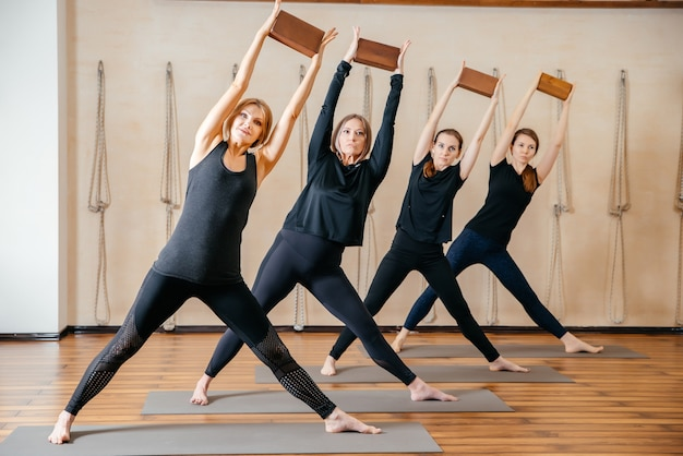 Group of women practicing yoga stretching using wooden blocks, exercise for spine and shoulders flexibility