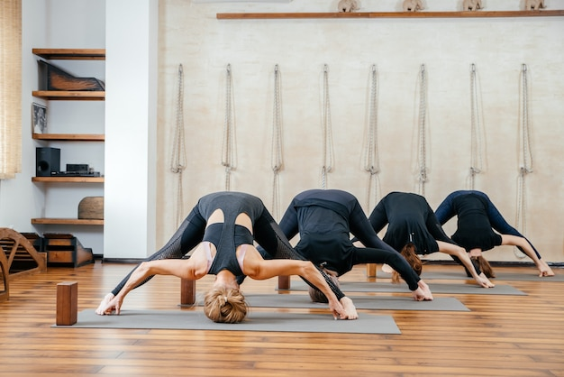 Group of women practicing yoga stretching using wooden blocks, exercise for spine and shoulders