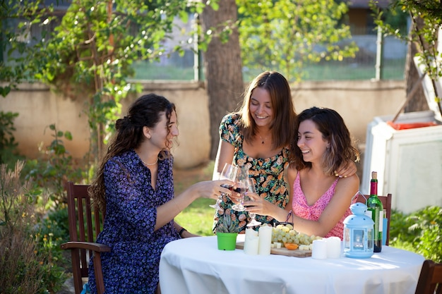 Group of women sitting on the backyard and having drinks at party outdoors.  friendship concept with young people enjoying harvest time together.