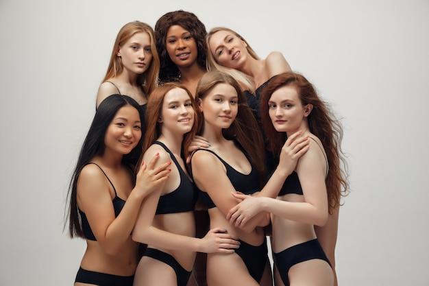 Gruppo di donne con diverso corpo ed etnia in posa insieme per mostrare il potere e la forza della donna.