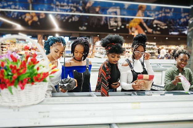 Group of women with shopping carts near refrigerator choose packs of dumplings in the supermarket