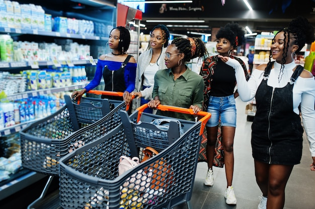 Group of women with shopping carts near refrigerator shelf selling dairy products made from milk in the supermarket