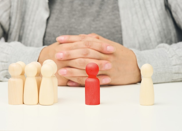 Group of wooden figures, and one standing. between them is a red wooden figurine of the negotiator man. finding a compromise, discussion