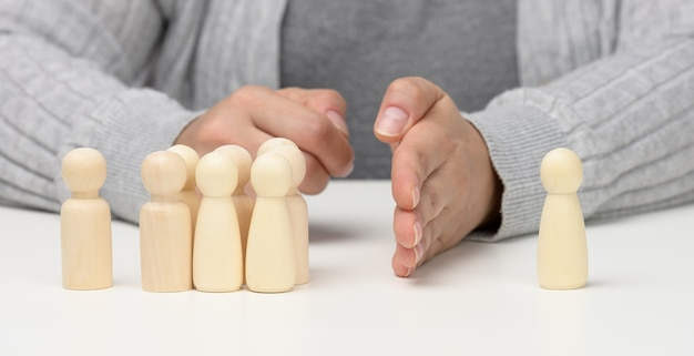 A group of wooden figures stands opposite one figure, with a hand between them. the concept of reconciliation of opponents, the end of bullying, the search for a compromise