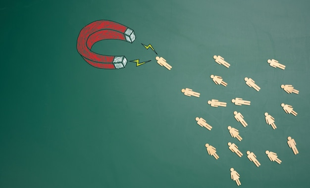 Group of wooden little men are attracted by a magnet on a green background. personnel search concept, team recruitment