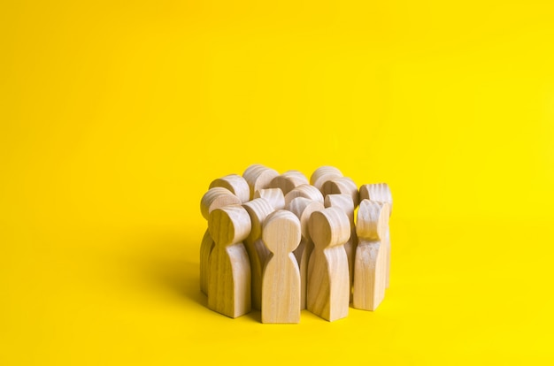 Group of wooden people figurines on a yellow background. crowd, meeting, social activity.