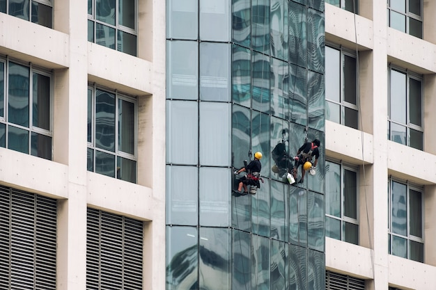Group of worker men hanging sling with cleaning the window of modern high rise building