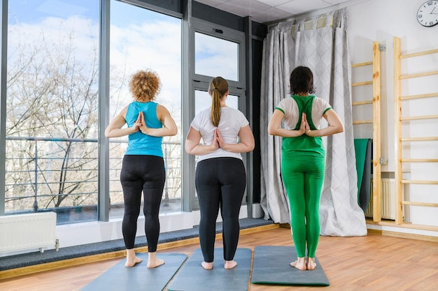 Group workout training yoga fitness exercises of three women stay back with hands in namaste