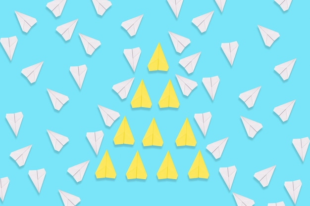 A group of yellow paper airplanes purposefully flies among the white planes. blue background. flat lay. the concept of leadership and teamwork.