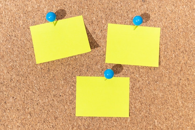 Group of yellow sticky notes on a cork board for adding text. template mock up