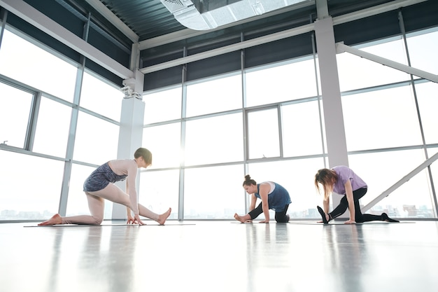 Group of young active females in sportswear keeping one knee on mat while stretching legs forwards during yoga exercise in gym