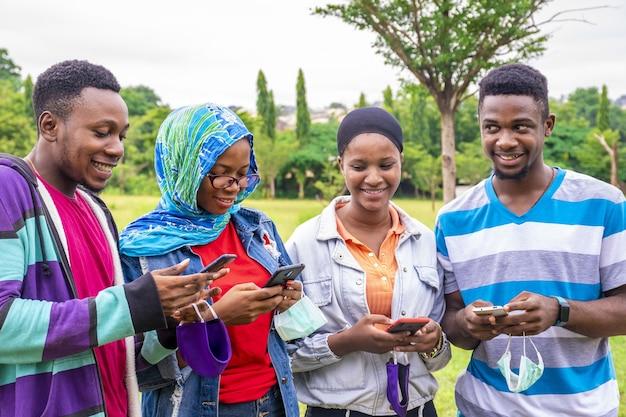 Gruppo di giovani amici africani con maschere che usano i loro telefoni in un parco