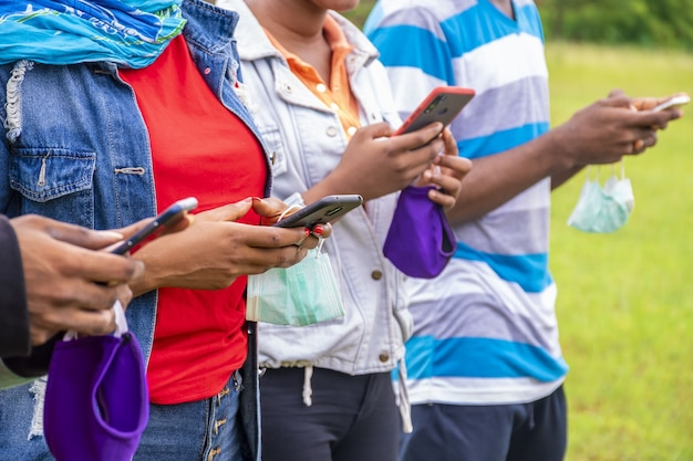 Group of young african friends with facemasks using their phones at a park