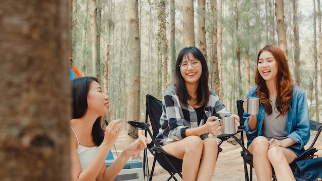 Group of young asia camper friends sitting in chairs by tent in forest