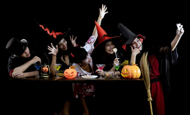 Group young asian in costume celebrate halloween party and selfie on black wall.. costume ghost, evil of group teen thai with fun.