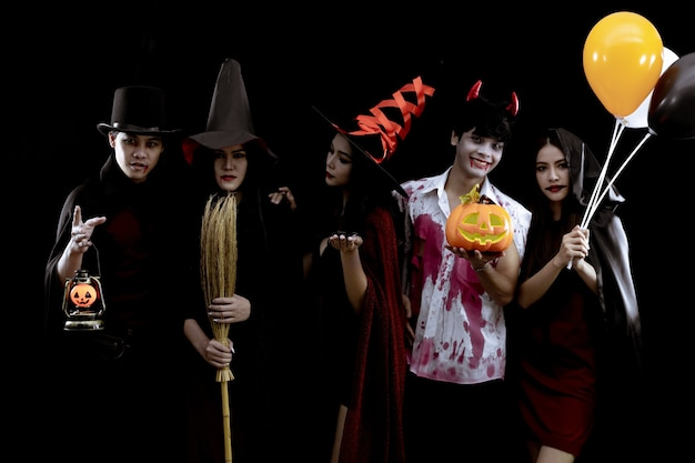 Group young asian in costume halloween party on black wall with concept for halloween fashion festival . gang of teen asian in cosplay halloween. costume ghost, evil of group teen thai.