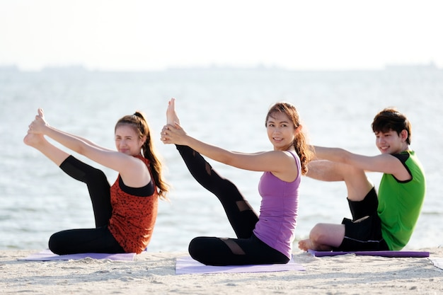 Group of young asian healthy people practicing yoga on the beach