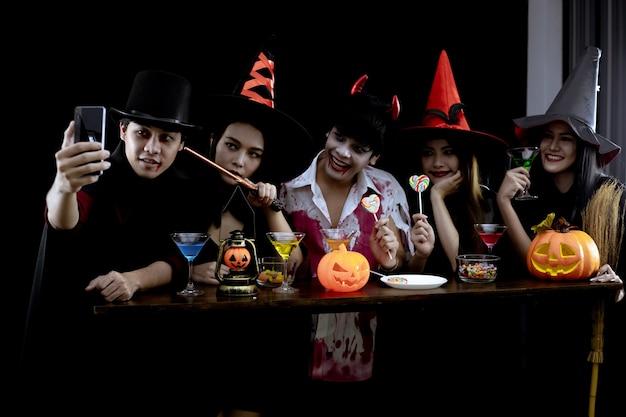 衣装を着た若いアジア人のグループは、黒い背景でハロウィーンパーティーと自分撮りを祝います。コスプレハロウィーンの十代のアジア人のギャング。コスチュームゴースト、楽しいグループティーンタイの悪。