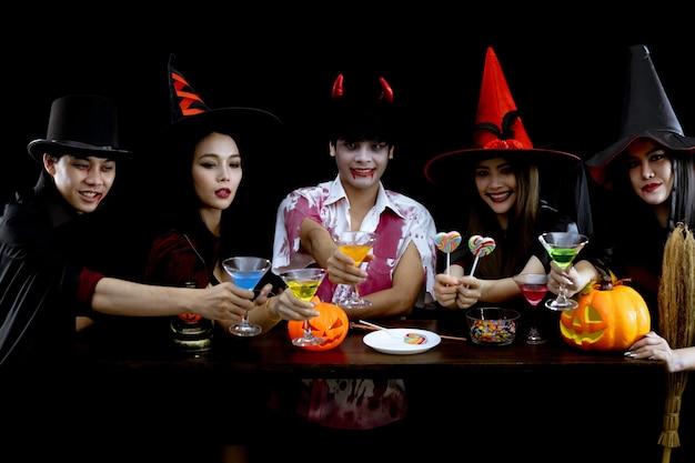 의상을 입은 젊은 아시아인 그룹은 할로윈 패션 축제를 위한 개념으로 검은 배경에서 할로윈 파티를 축하합니다. 코스프레 할로윈에서 십대 아시아의 갱. 그룹 틴 타이의 의상 귀신, 악마.