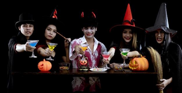 Группа молодых азиатских в костюмах празднует вечеринку в честь хэллоуина на черной стене с концепцией для фестиваля моды хэллоуина. банда азиатских подростков в косплее на хэллоуин. костюм привидения, злобной группы тайских подростков.